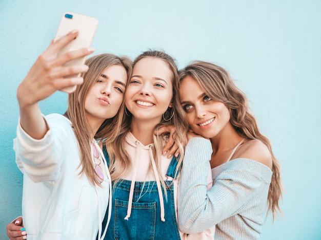 Три молодые улыбающиеся женщины битник в летней одежде. девушки, делающие фотографии автопортрета селфи на смартфоне. модели, позирующие на улице около стены. женщина, показывающая положительные эмоции лица