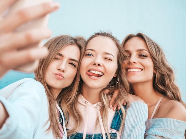 Три молодые улыбающиеся битник женщины в летней одежде. девушки, делающие фотографии автопортрета селфи на смартфоне. модели, позирующие на улице около стены. женщина, показывающая положительные эмоции лица. показывая язык