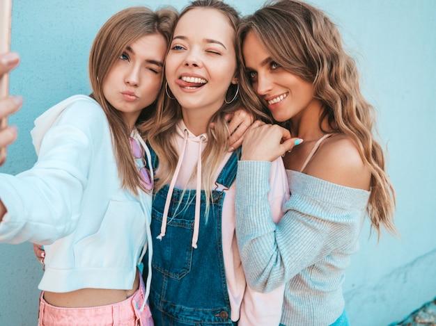 Три молодые улыбающиеся битник женщины в летней одежде. девушки, делающие фотографии автопортрета селфи на смартфоне. модели, позирующие на улице около стены. женщина, показывающая положительные эмоции лица. показывает язык