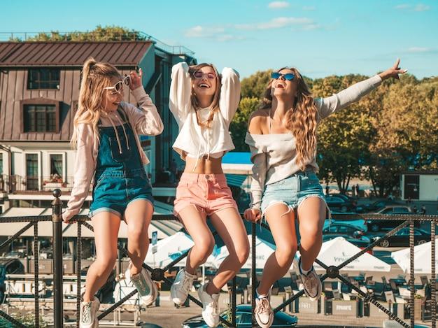 Три молодые красивые улыбающиеся хипстерские девушки в модной летней одежде