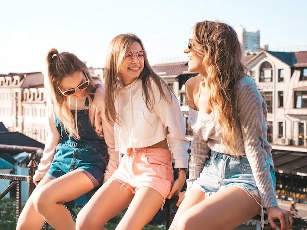 Сексуальные женщины сидят на перилах на улице они что-то общаются и обсуждают