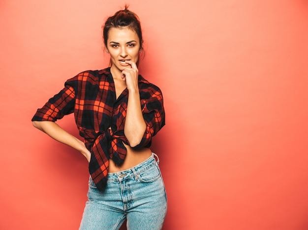 トレンディな夏の若い美しい笑みを浮かべて内気な少女の肖像格子縞のシャツとジーンズの服。セクシーな屈託のない女性がスタジオでピンクの壁に近いポーズします。化粧なしのポジティブモデル