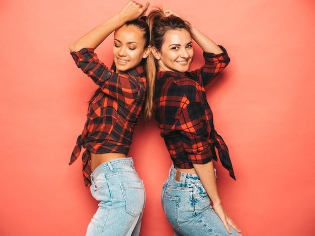 Две молодые красивые улыбающиеся брюнетки-хипстерские девушки в модной схожей клетчатой рубашке и джинсовой одежде. сексуальные беззаботные женщины, позирует возле розовой стены в студии. позитивные модели с удовольствием