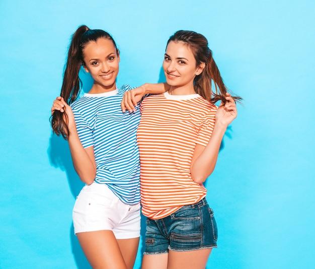 Две молодые красивые улыбающиеся брюнетки-хипстерские девушки в модных похожих полосатых летних ярких рубашках. сексуальные беззаботные женщины, позирует возле синей стены в студии. позитивные модели с удовольствием