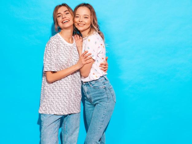 Сексуальные беззаботные женщины позируют возле синей стены. веселые позитивные модели