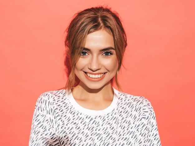肯定的な女性の笑顔。スタジオでピンクの壁に近いポーズ面白いモデル