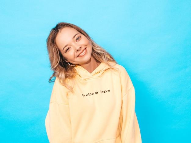 Портрет молодой красивой улыбающейся девушки в модной летней хипстерской желтой толстовке с капюшоном