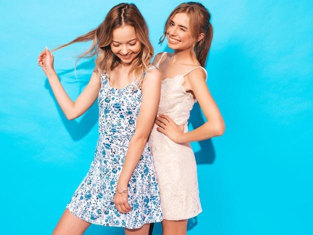 Две молодые красивые улыбающиеся хипстерские девушки в модных летних повседневных платьях. сексуальные беззаботные женщины позируют возле синей стены. веселиться и обниматься. модели показывают хорошие отношения. женщина без макияжа