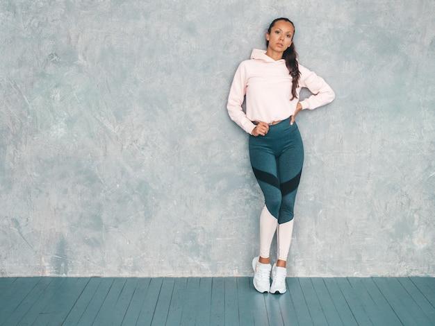 自信を持って探しているスポーツウェアで自信を持ってフィットネス女性の肖像画。灰色の壁の近くのスタジオでポーズをとる女性