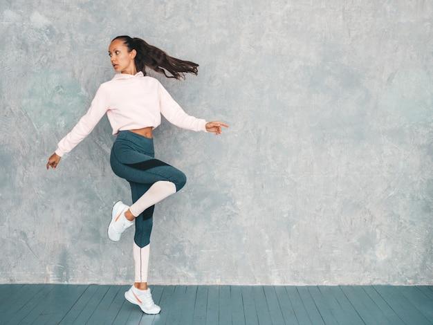 Портрет уверенной женщины фитнеса в спортивной одежде смотря уверенно. женский прыгать в студии около серой стены
