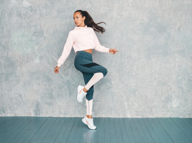 自信を持って探しているスポーツウェアで自信を持ってフィットネス女性の肖像画。灰色の壁の近くのスタジオでジャンプ女性