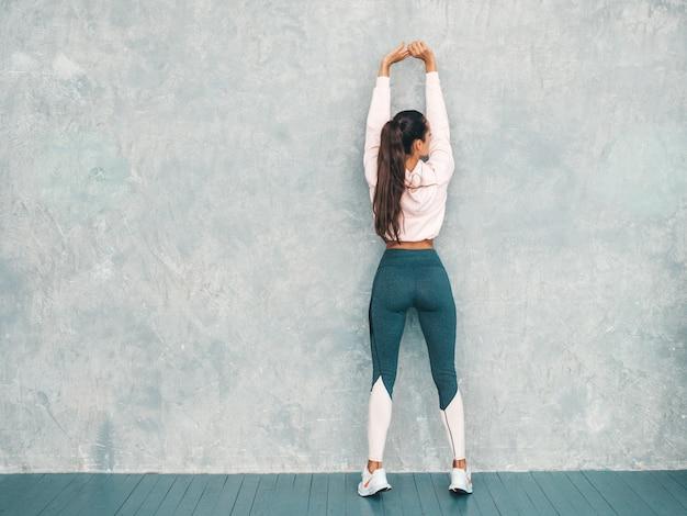 自信を持って探しているスポーツウェアのフィットネス女性の背面図スタジオの灰色の壁の近くのトレーニングの前にストレッチする女性