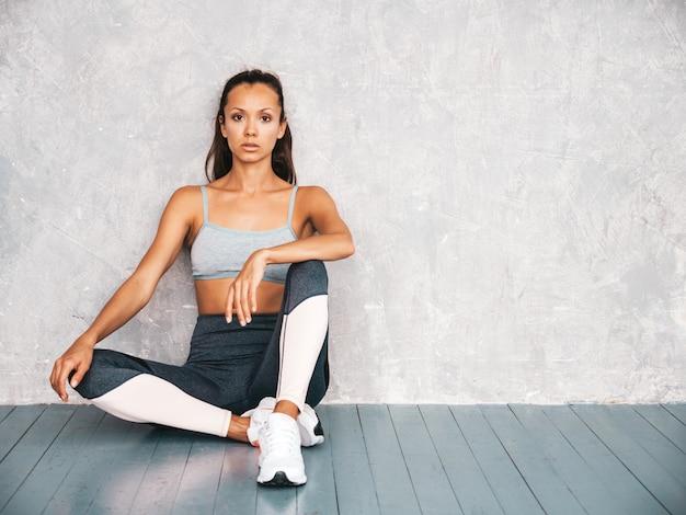 完璧な日焼けした体を持つ美しいモデル。灰色の壁の近くのスタジオに座っている女性