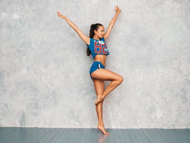 Девушка прыгает в студии возле серой стены