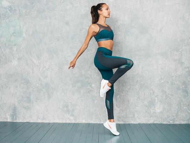 Портрет женщины фитнеса в спортивной одежде смотря уверенно