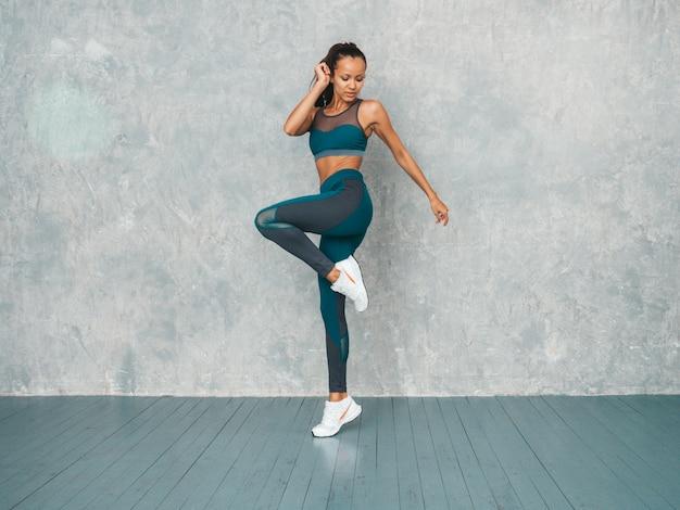 自信を持って探しているスポーツウェアのフィットネス女性の肖像画。スポーツウェアを着ている若い女性。完璧な日焼けした体を持つ美しいモデル。灰色の壁の近くのスタジオでジャンプする女性
