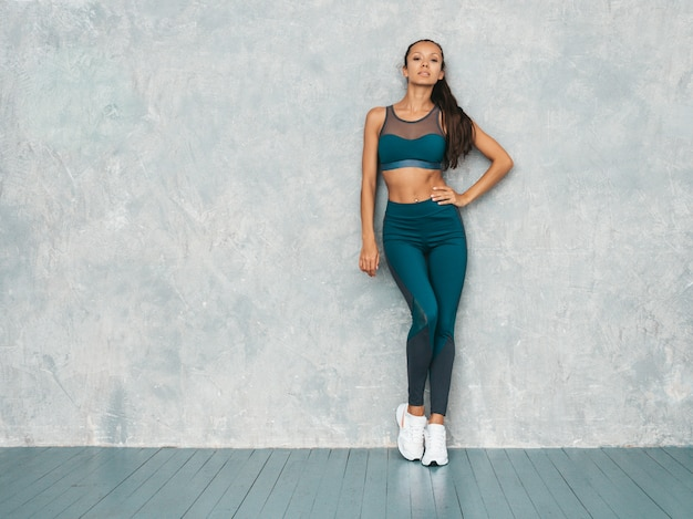 スポーツウェアを着ている若い女性。完璧な日焼けした体を持つ美しいモデル。灰色の壁の近くのスタジオでポーズをとる女性