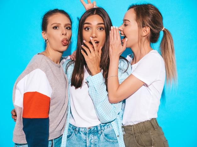 Сексуальные беспечальные женщины представляя около голубой стены в студии. позитивные модели сходят с ума и веселятся. делимся секретами, сплетничаем