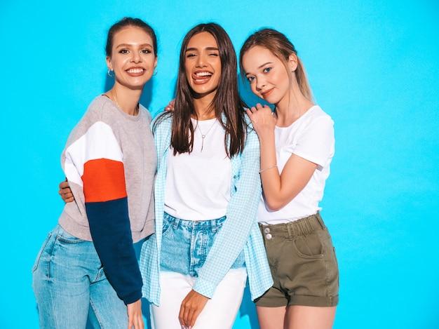 Сексуальные беспечальные женщины представляя около голубой стены в студии. позитивные модели развлекаются и обнимаются