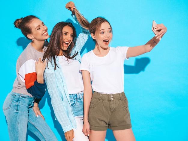 Девушки, делающие фотографии автопортрета селфи на смартфоне. модели, позирующие около синей стены в студии, женщина, показывающая положительные эмоции лица