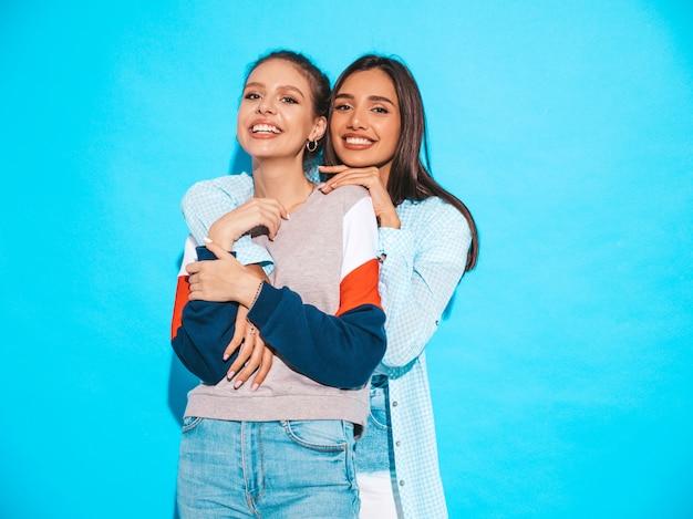 Две молодые красивые улыбающиеся белокурые хипстерские девочки в модной летней красочной футболке одеваются. сексуальные беззаботные женщины позируют возле синей стены. веселые позитивные модели