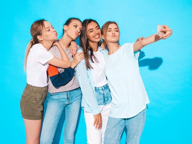 スマートフォンでセルフポートレート写真を撮る女の子。スタジオの青い壁の近くでポーズをとるモデル、肯定的な顔の感情を示す女性