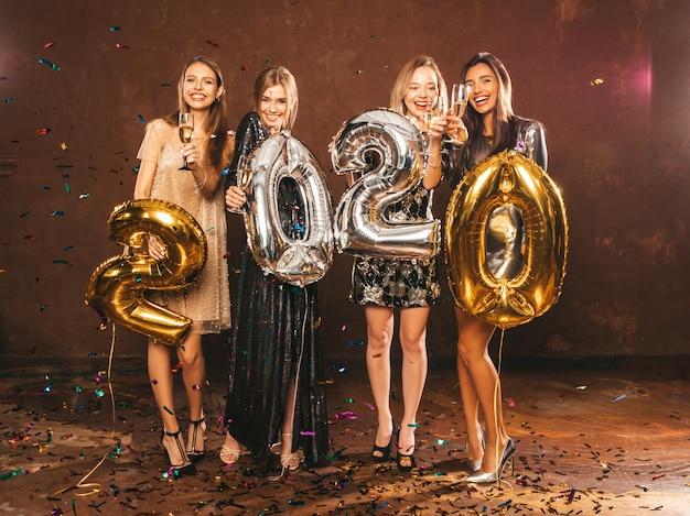Красивые женщины празднуют новый год. счастливые великолепные девушки в стильных сексуальных платьях