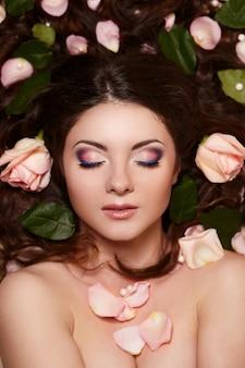Портрет красивой брюнетки с длинными вьющимися волосами и ярким макияжем с цветами в волосах