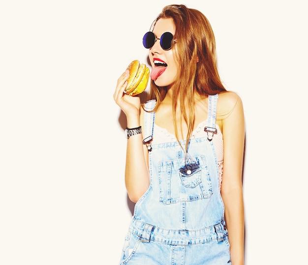 ハンバーガーを食べて美しいスタイリッシュな若い女性の肖像画