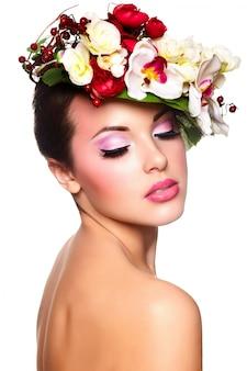 Портрет красивой стильной молодой женщины с яркими цветами на голове
