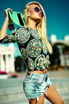 Портрет красивой стильной молодой женщины с скейтборд