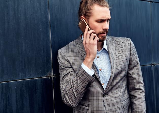 Красивый мужчина в сером клетчатом костюме, говорить с смартфон
