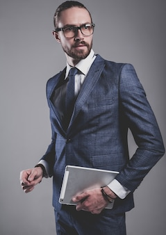 Портрет модельер красивый бизнесмен, одетый в элегантный синий костюм в очках