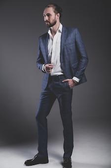 グレーでポーズエレガントな青いスーツに身を包んだハンサムなファッションスタイリッシュな流行に敏感なビジネスマンモデルの肖像画