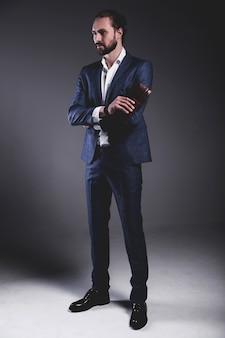 Портрет красивый модный стильный битник бизнесмен модель, одетый в элегантный синий костюм позирует на сером