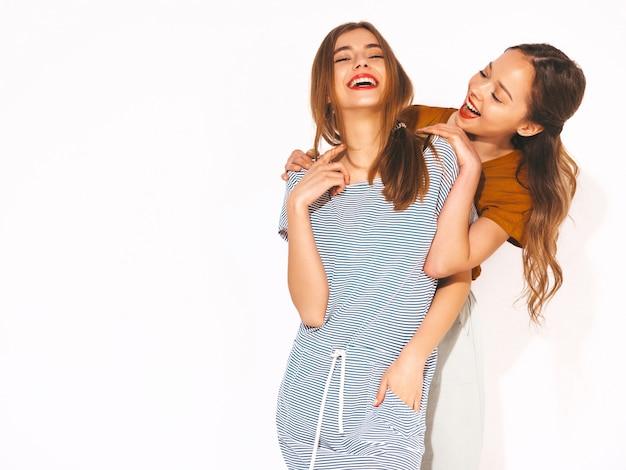 Две молодые красивые улыбающиеся девушки в модной летней повседневной одежды. сексуальные беззаботные женщины. позитивные модели, обнимаются