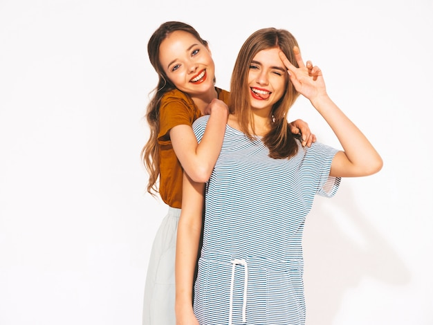 Две молодые красивые улыбающиеся девушки в модной летней повседневной одежды. сексуальные беззаботные женщины. позитивные модели
