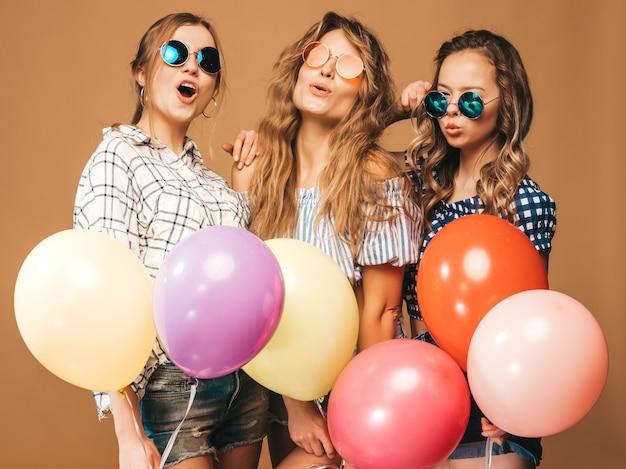 Три улыбающиеся красивые женщины в клетчатой рубашке летней одежды и солнцезащитные очки. девочки позируют. модели с разноцветными шарами. веселимся, готовимся к празднованию дня рождения