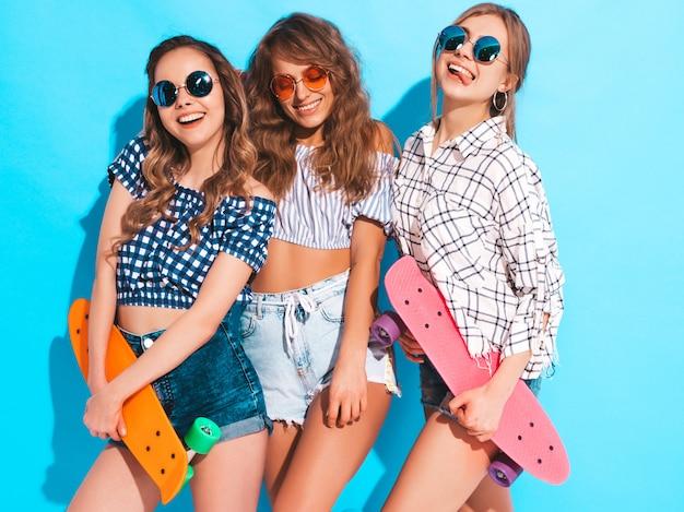 Три молодые стильные улыбающиеся красивые девушки с красочными пенни скейтборды. женщины в летней одежде позирует в солнцезащитные очки. веселые позитивные модели