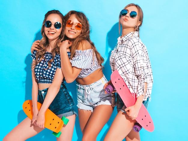 Три молодые стильные сексуальные улыбающиеся красивые девушки с красочными пенни скейтборды. женщины в клетчатой рубашке летом позирует в солнцезащитные очки. веселые позитивные модели