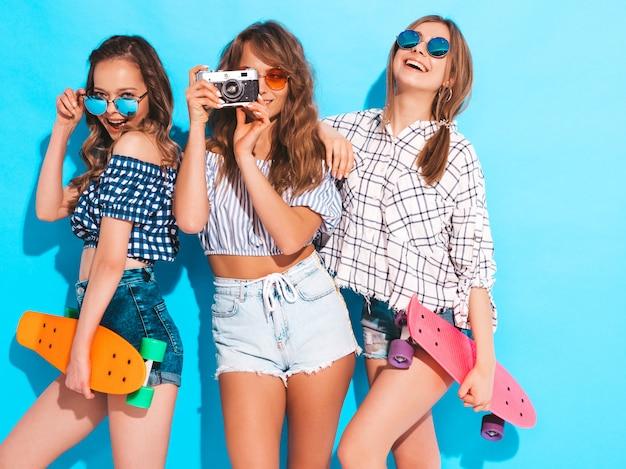 Три сексуальные красивые стильные улыбающиеся девушки с красочными пенни скейтборды. женщины в клетчатой рубашке летом позируют. модели снимают на ретро фотоаппарат