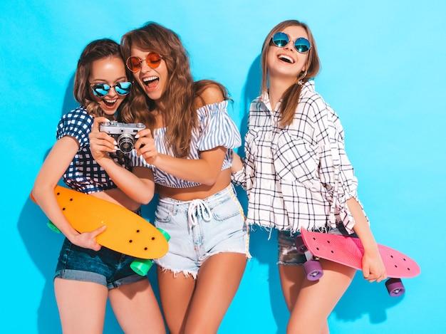 Три красивые стильные улыбающиеся девушки с красочными пенни скейтборды. женщины в клетчатой летней рубашке одеваются. фотосъемка на ретро фотоаппарате