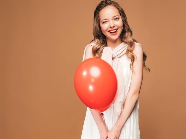 トレンディな夏の白いドレスでポーズをとって興奮している若い女の子。赤い風船のポーズで女性モデル。パーティーの準備ができて