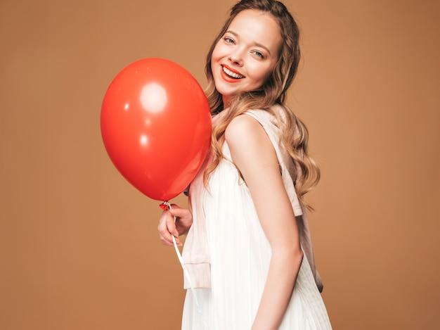 トレンディな夏の白いドレスでポーズをとって興奮している若い女の子の肖像画。赤い風船のポーズで笑顔の女性。パーティーの準備ができたモデル