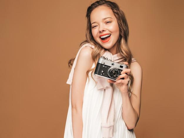 インスピレーションと写真を撮ると白いドレスを着て陽気な笑顔の若い女性の肖像画。レトロなカメラを保持している女の子。モデルのポーズ