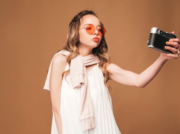インスピレーションと写真を撮ると白いドレスを着て陽気な若い女性の肖像画。レトロなカメラを保持している女の子。モデルのポーズ。