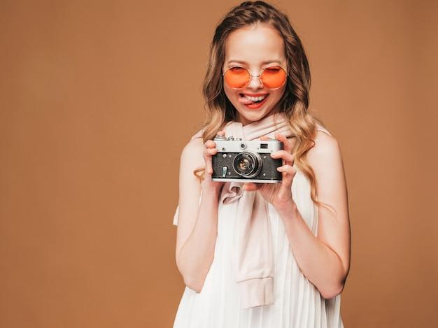 Портрет жизнерадостной молодой женщины принимая фото с воодушевленностью и нося белое платье. девушка держит ретро камеры. модель позирует