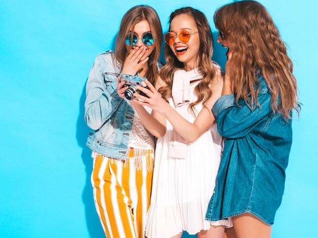 Три молодые красивые улыбающиеся девушки в модной летней повседневной одежды и солнцезащитные очки. сексуальные беззаботные женщины позируют. фотографировать на ретро камеру