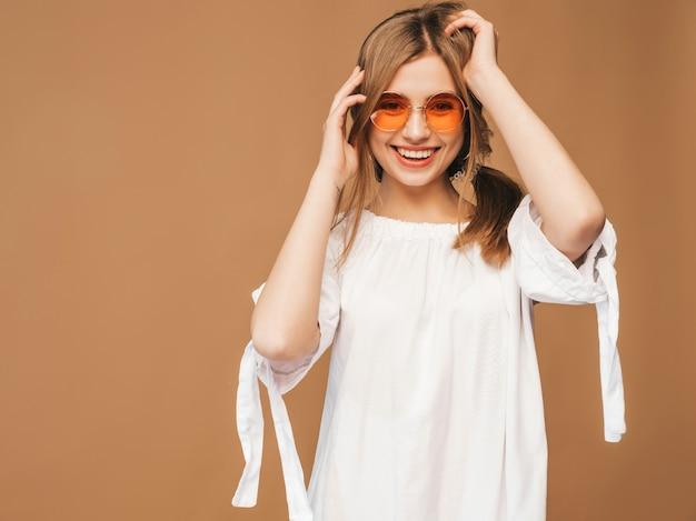 ピンクの唇と美しい笑顔かわいいモデルの肖像画。夏の白いドレスの女の子。サングラスでポーズをとるモデル