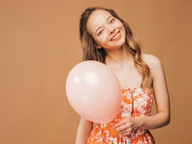 トレンディな夏のカラフルなドレスでポーズをとって興奮している若い女の子の肖像画。ピンクのバルーンポーズで笑顔の女性。パーティーの準備ができたモデル